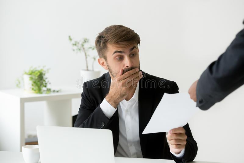 Surprised confused caucasian employee receiving dismissal notice. Letter or document with unexpected news from african boss, worried shocked office worker royalty free stock photography