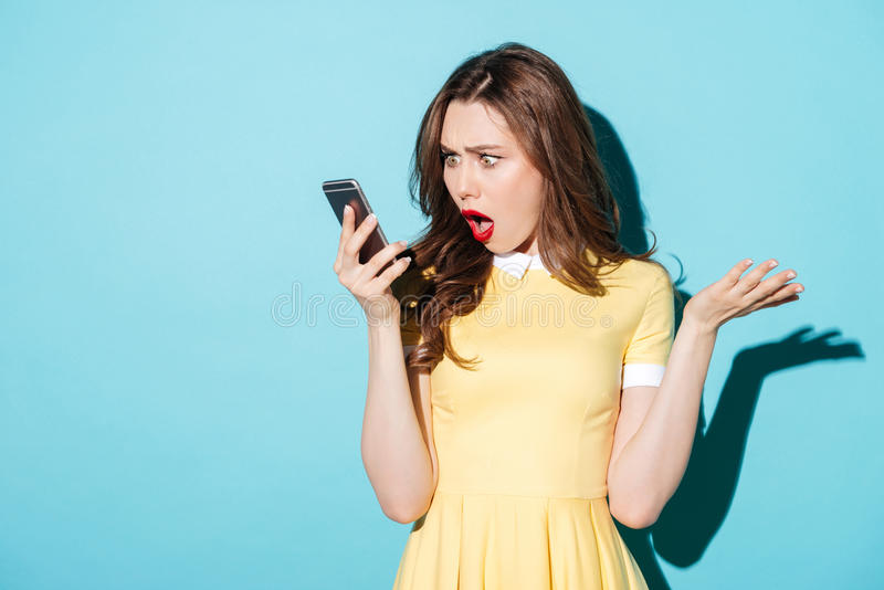 Surprised confused woman in dress looking at mobile phone royalty free stock photo