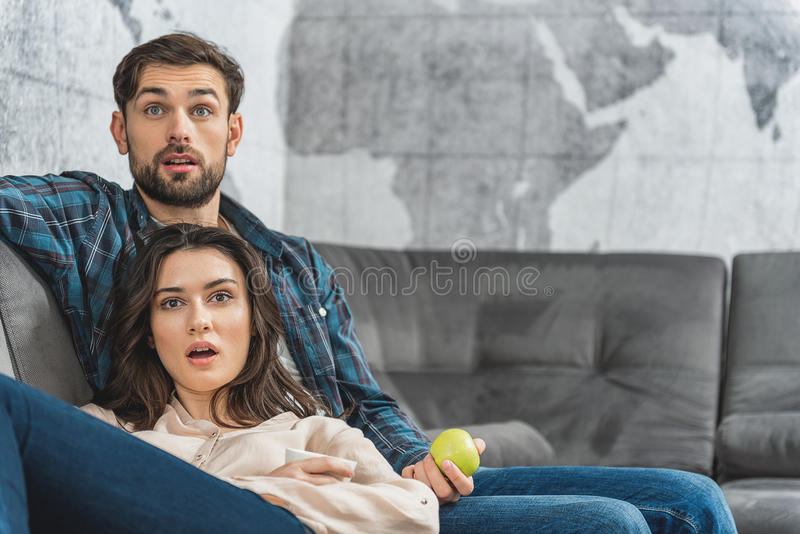 Surprised couple entertaining with tv at home stock photography