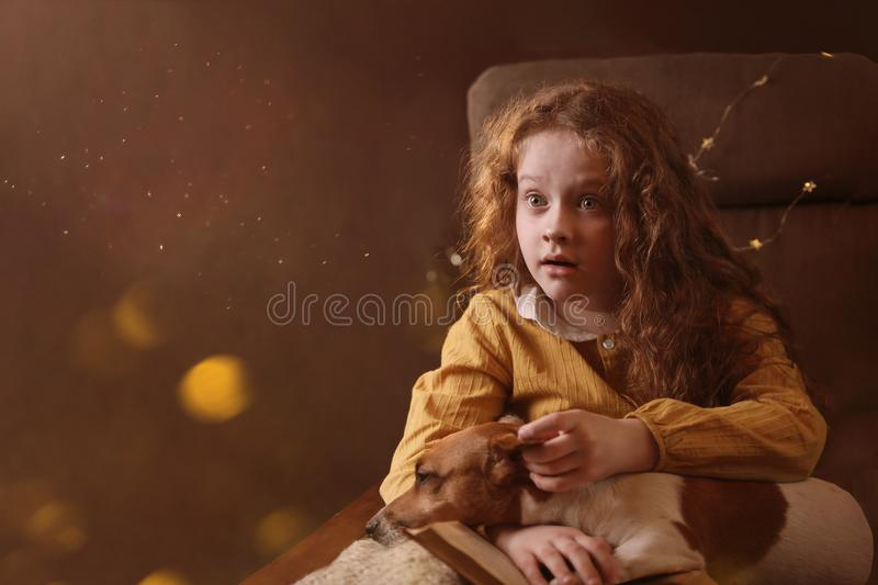 Surprised curly haired girl with a book and dog on her knees. royalty free stock photography