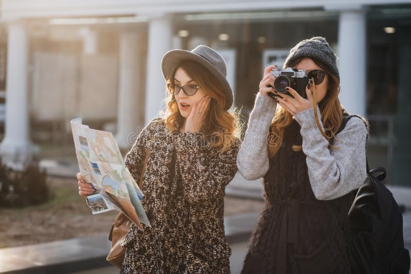 Surprised curly woman in glasses looking at map, touching face while her friend making photo of sights. Attractive stock images
