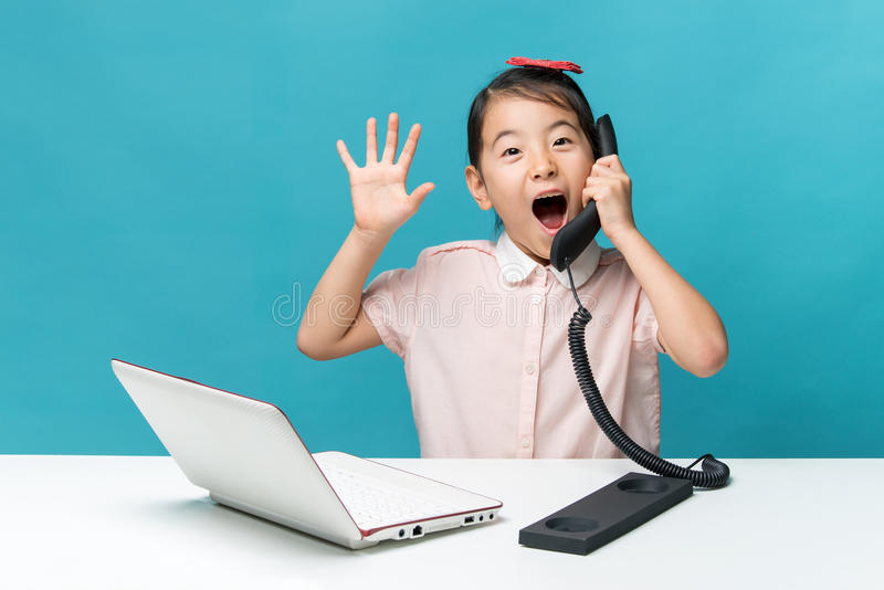 Surprised, Cute asia little girl is sitting at table with her white laptop and a telephone, isolated over blue stock images