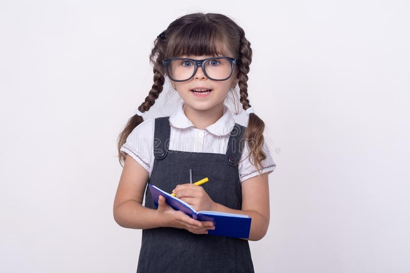Surprised cute child in eyeglasses writing in notebook using pencil. Five or six years old  school kid,  on white royalty free stock photos