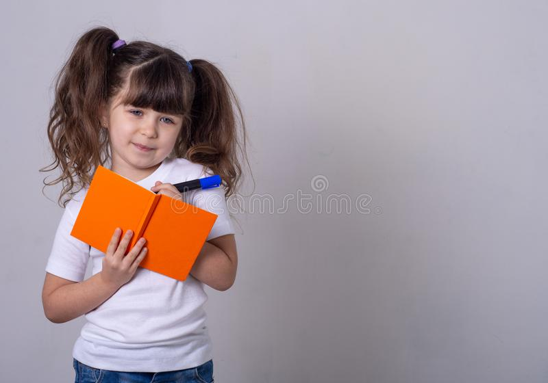 Surprised cute child writing in notebook using pencil, keeping mouth wide open. Four or five years old kid, isolated royalty free stock photos