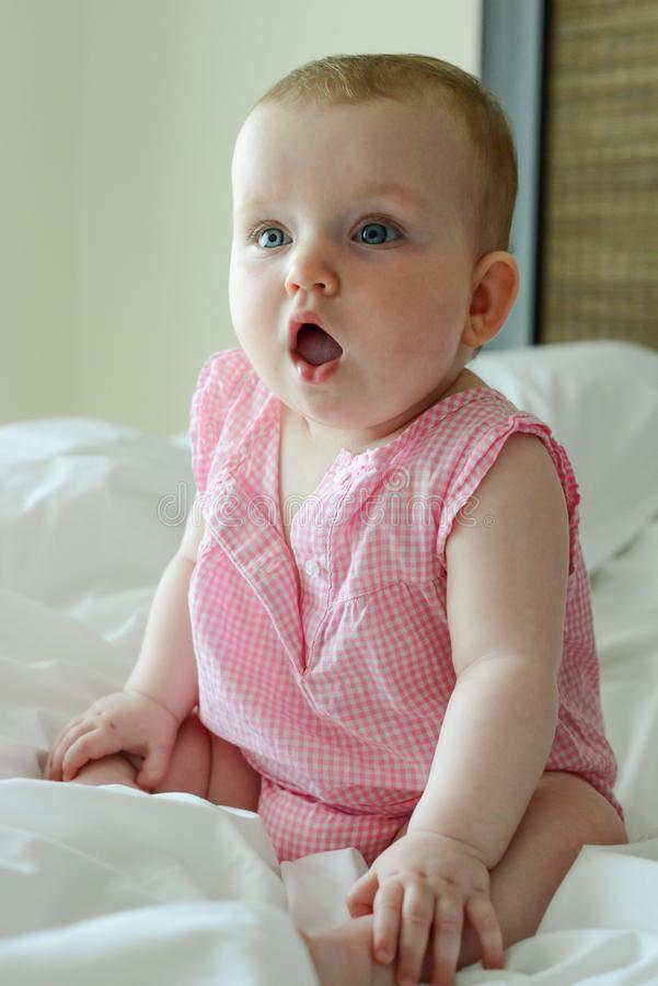 Surprised cute little Caucasian baby sits on the bed. royalty free stock photos