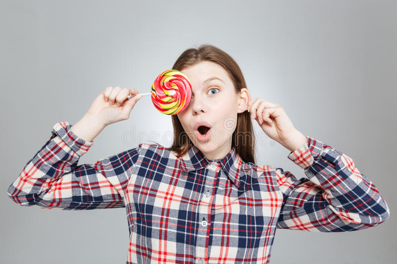 Surprised cute teenage girl covered her eye with lollipop royalty free stock photos