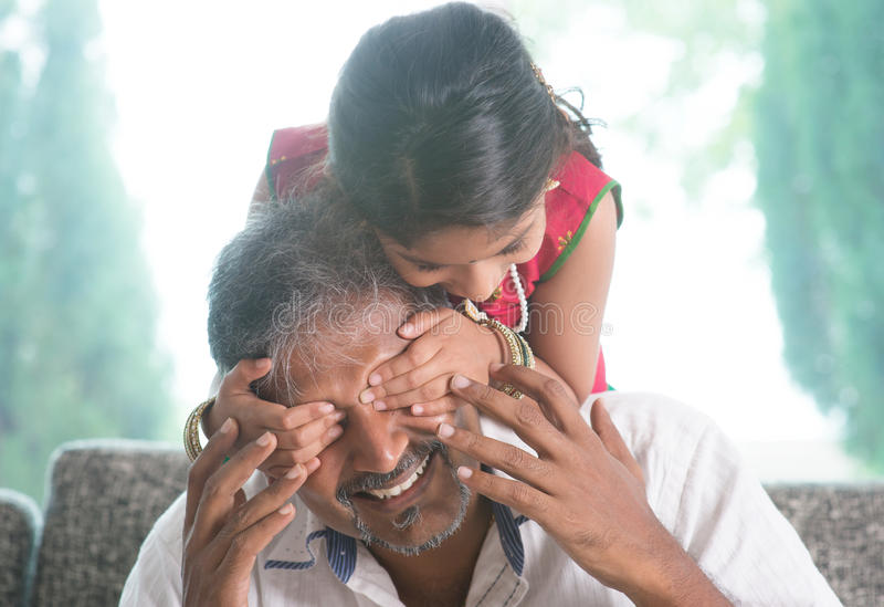 Surprised daddy. Happy Indian family at home. Asian girl surprising her father by covering daddy eyes. Parent and child indoor lifestyle royalty free stock images