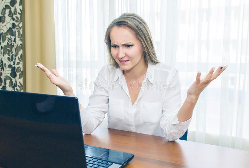 Surprised and dissatisfied girl expresses emotion looking at the laptop. stock photo