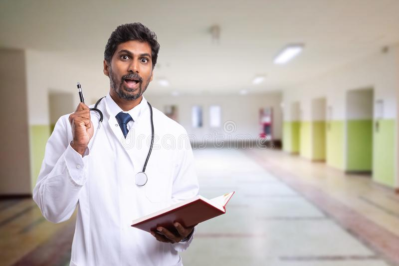 Surprised doctor holding pen and notebook. Surprised indian doctor or medic man holding pen and notebook as good idea looking at notes concept with hospital royalty free stock images