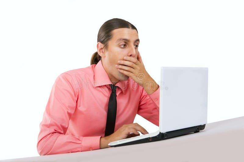Surprised a effrayé le jeune homme avec l'ordinateur portable images libres de droits