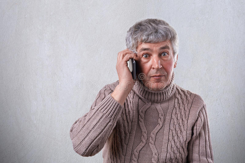 A surprised elderly man in sweater having gray hair round dark eyes and wrinkles on his face communicating over the telephone whil royalty free stock images