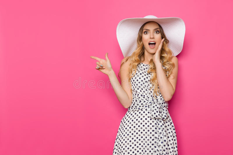 Surprised Elegant Woman In Sun Hat Is Holding Hand On Chin And Pointing. Beautiful young woman in white dotted summer dress and sun hat is pointing at copy space stock images