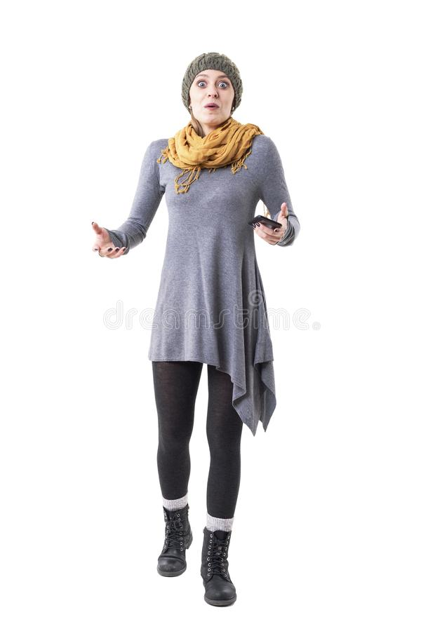 Surprised expression amazed young stylish hipster woman holding mobile phone looking at camera stock images