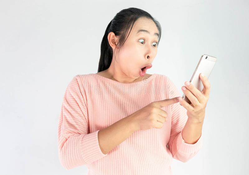 Surprised face of Asian woman shocked what she see in the smartphone, Isolated on white background royalty free stock photos