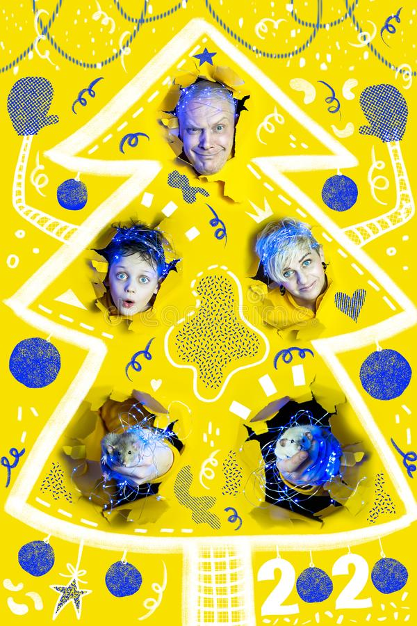 Surprised faces of people and rats in New Year`s garlands peek out of holes in yellow paper. The large size of each portrait royalty free stock photo