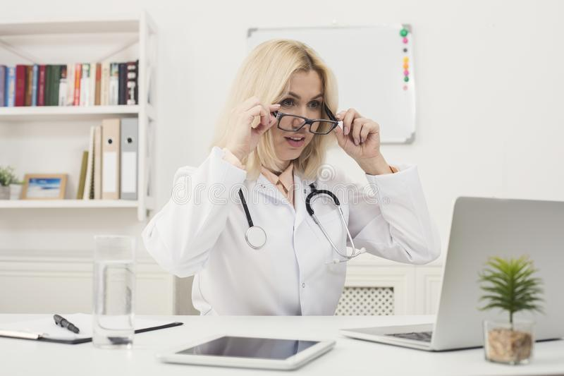 Surprised doctor with glasses sitting at desktop royalty free stock photo