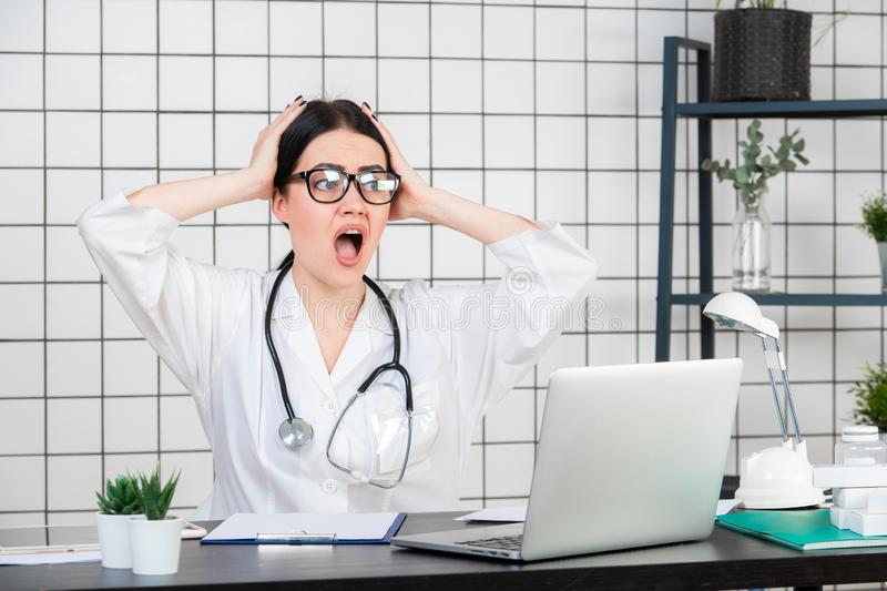 Surprised female doctor looking at laptop. Physician at her working office. Unexpected news or medical tests results stock photography