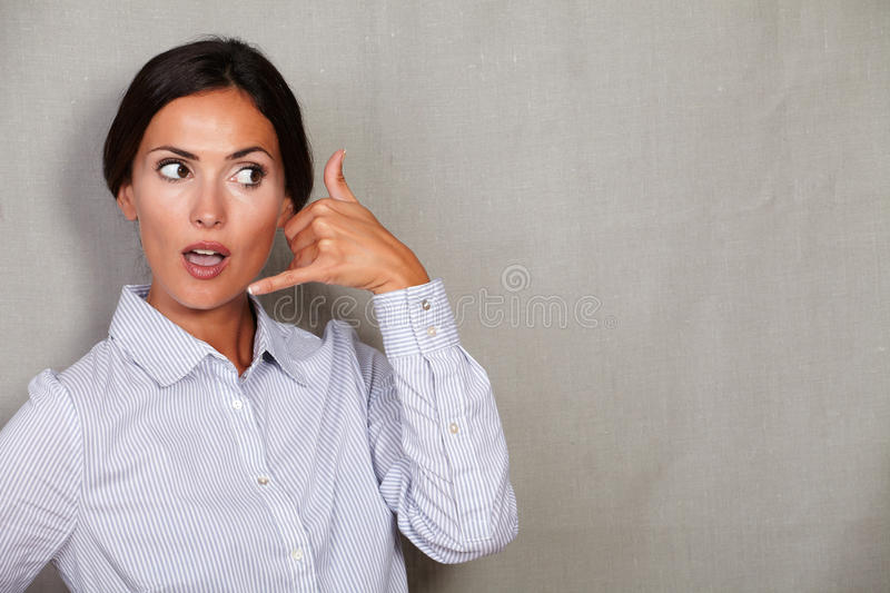 Surprised female gesturing call with open mouth. Suprised adult female gesturing a call with open mouth and formal clothing on grey texture background - copy royalty free stock image