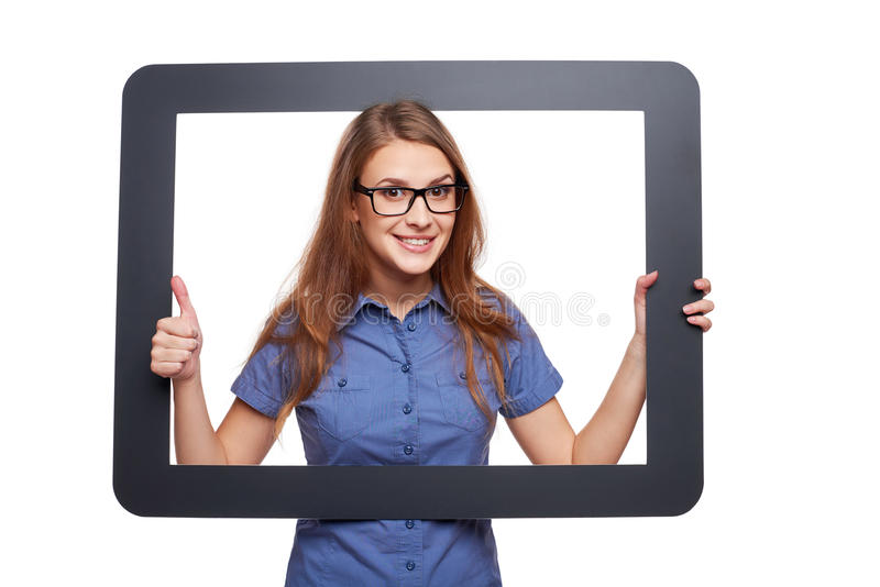 Surprised female peeping out of tablet frame. Happy smiling woman looking through frame and showing approving gesture, over white background royalty free stock photo