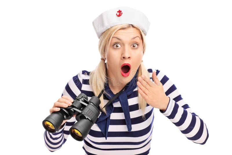 Surprised female sailor holding binoculars stock photos