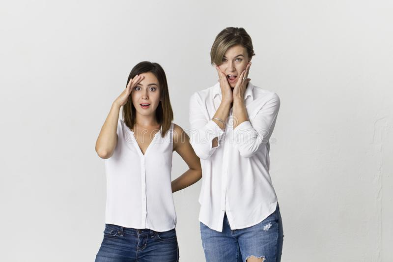 Surprised friends having fun at white background. Two girlfriends standing wearing white shirt and jeans royalty free stock image