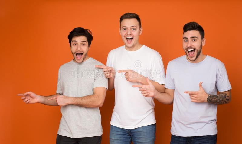 Surprised friends pointing fingers away, orange background royalty free stock images