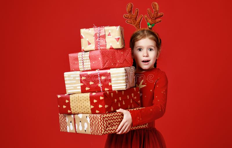 Surprised funny child girl in red Christmas reindeer costume with gifts on green   background royalty free stock photo