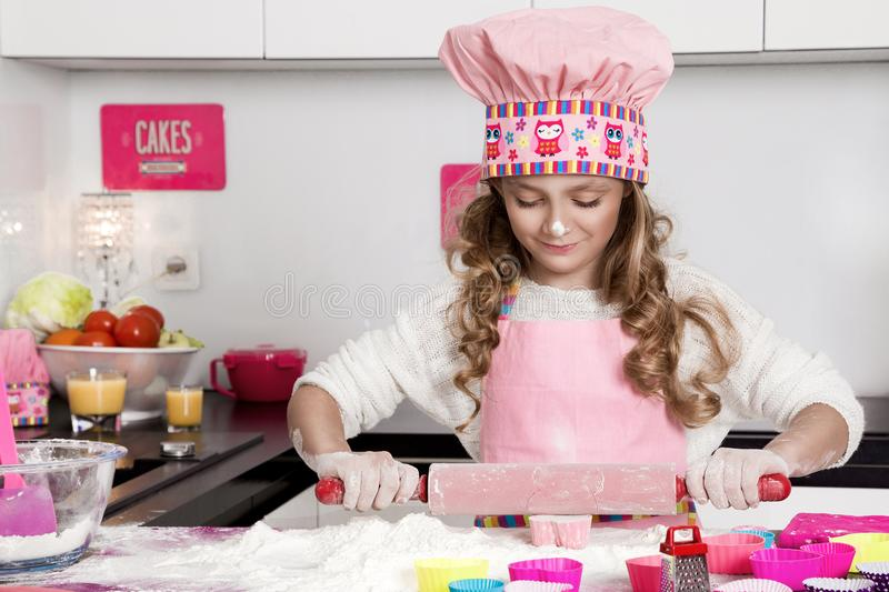 Surprised funny girl with pasta on the head. Standing in the kitchen in a pink apron smiled stock photos