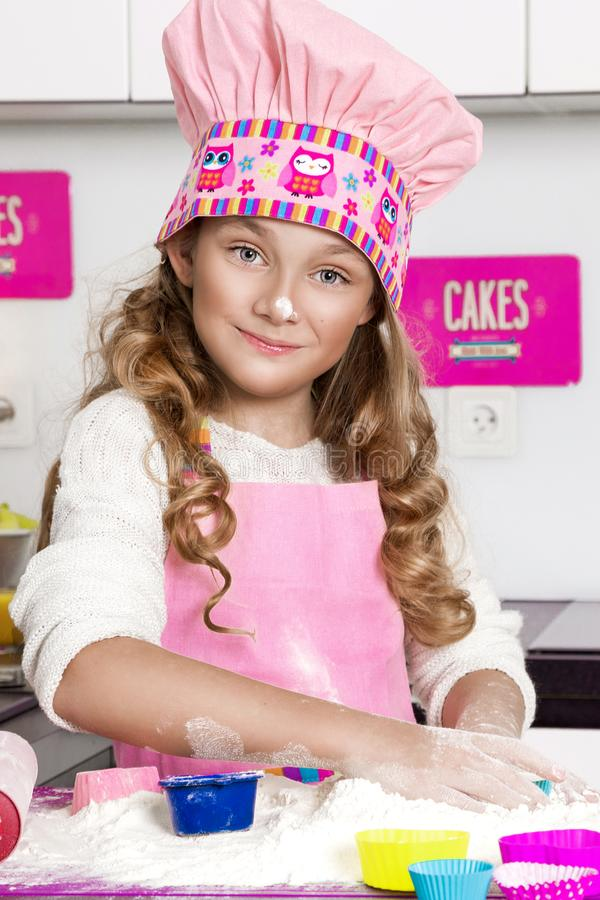 Surprised funny girl with pasta on the head. Standing in the kitchen in a pink apron smiled royalty free stock image