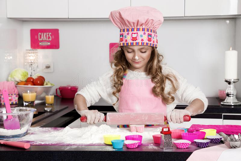 Surprised funny girl with pasta on the head. Standing in the kitchen in a pink apron smiled stock image