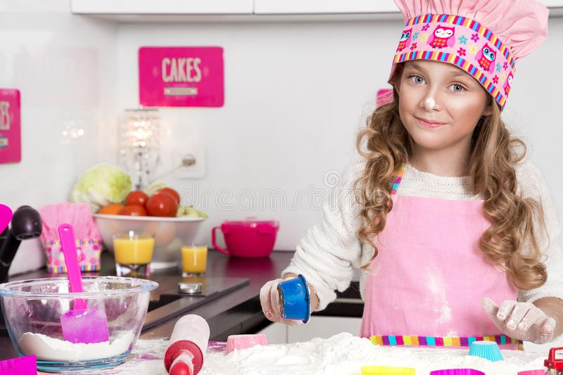 Surprised funny girl with pasta on the head. Standing in the kitchen in a pink apron smiled royalty free stock images