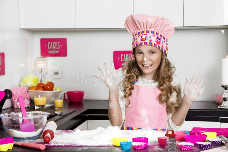 Surprised funny girl with pasta on the head. Standing in the kitchen in a pink apron smiled royalty free stock photos