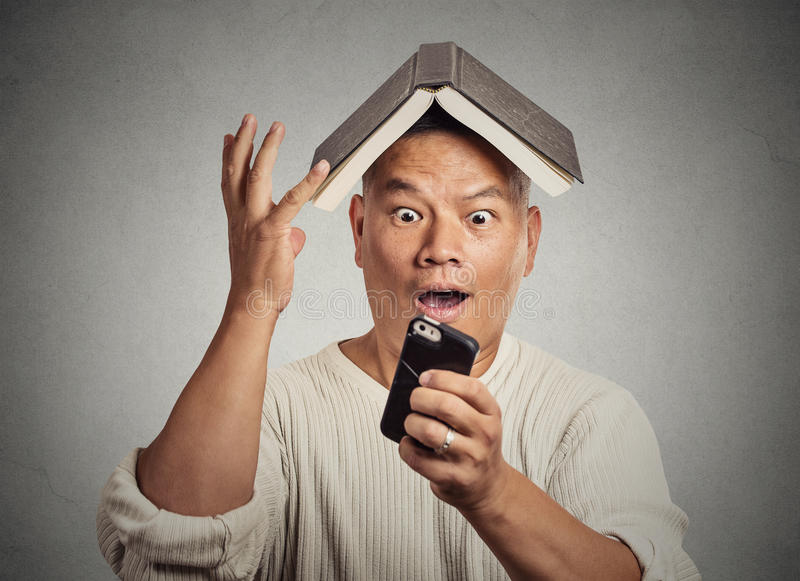 Surprised funny looking man with book on head reading news on smartphone royalty free stock image