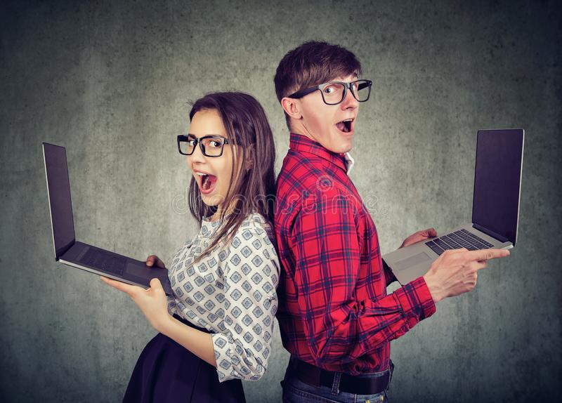 Surprised funny looking man and woman with new laptops stock images