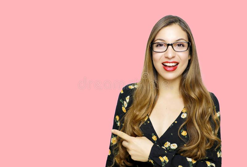 Surprised funny model girl wearing glasses and pointing finger empty copy space on open hand palm for text on pink background. royalty free stock photo
