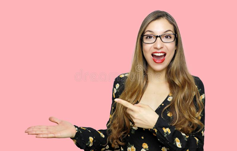 Surprised funny model girl wearing glasses and showing and pointing empty copy space on open hand palm for text on pink background stock images