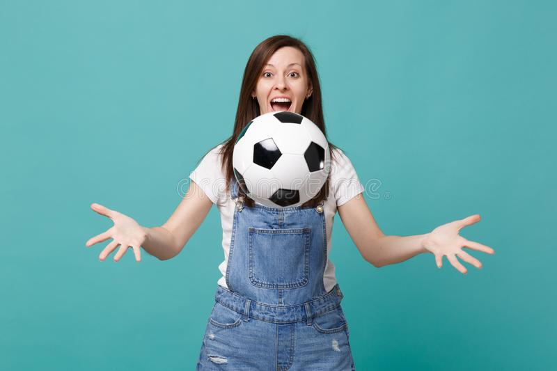 Surprised funny young woman football fan cheer up support favorite team throwing soccer ball isolated on blue turquoise. Background. People emotions, sport stock photo
