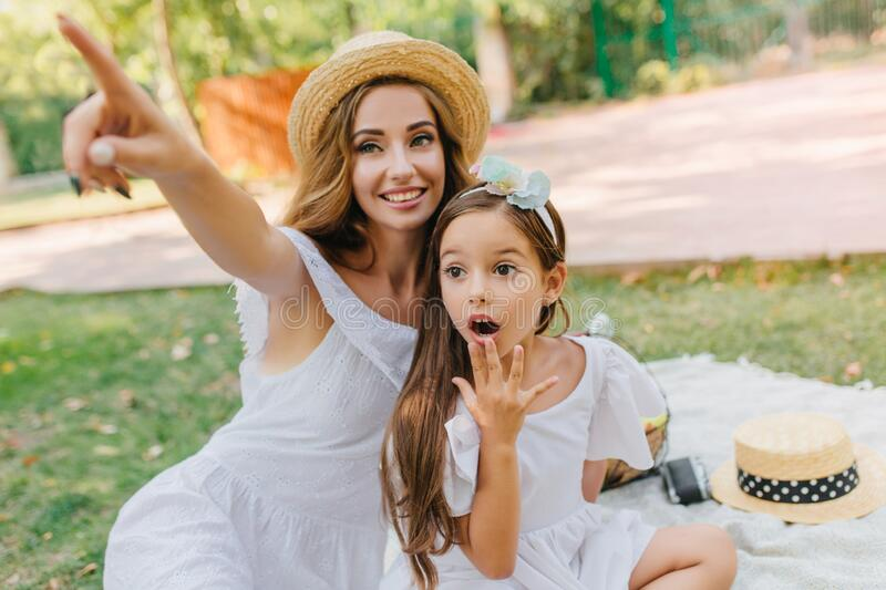 Surprised girl with big dark eyes looking where her mother pointing with finger. Charming young woman with long curly. Surprised girl with big dark eyes looking royalty free stock photos