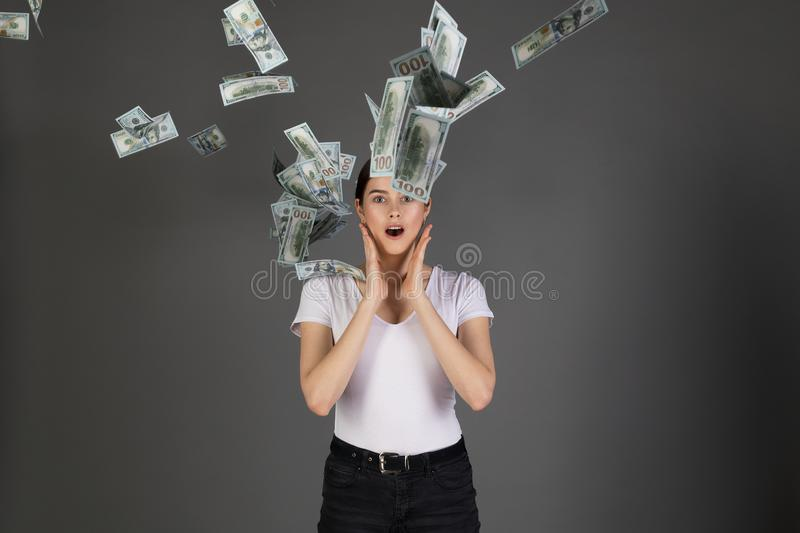 Surprised girl with hands near face, wearing white t-shirt. Under dropping of dollar money banknote,  over grey background royalty free stock image