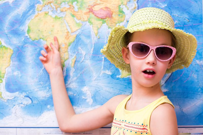 Surprised girl in a hat and sunglasses shows on a world map stock images