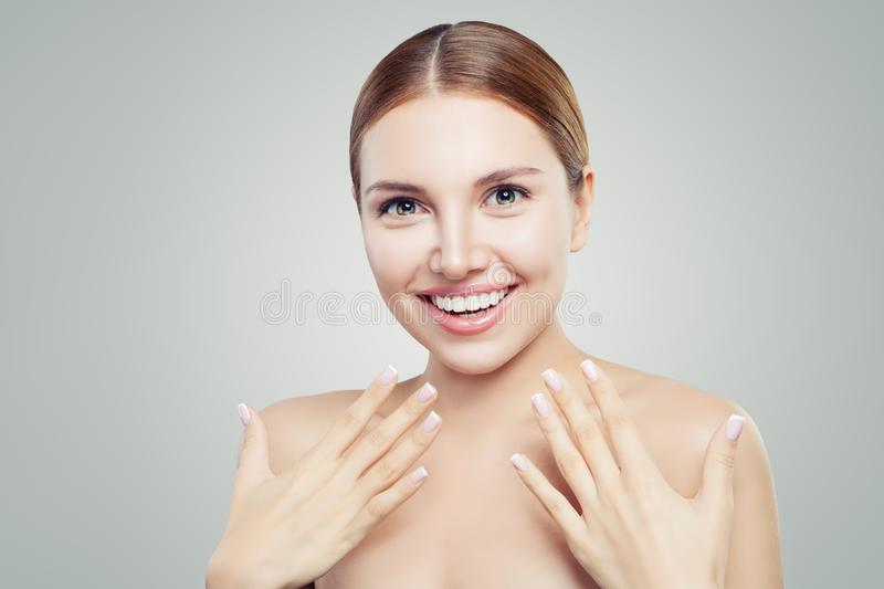 Surprised girl with healthy skin, cute smile and french manicure hand. Cosmetology offer concept stock photography