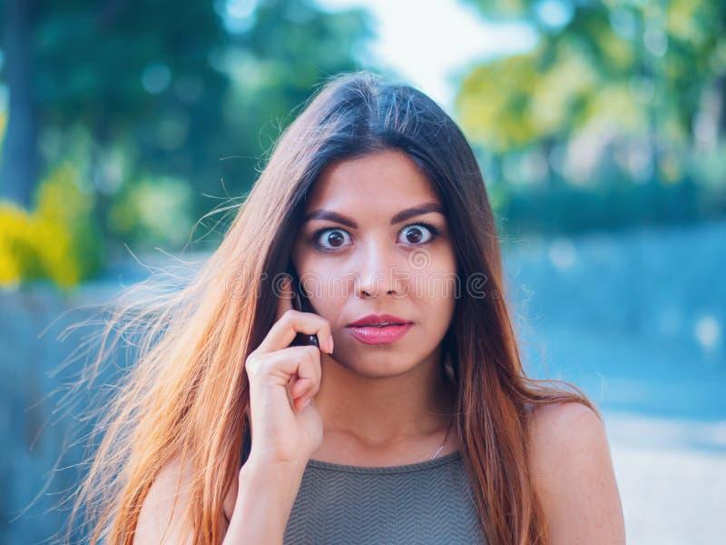 Surprised girl heard stunning news on phone. Gossip with girlfriend. Woman speaks on smartphone. Beautiful businesswoman royalty free stock photo