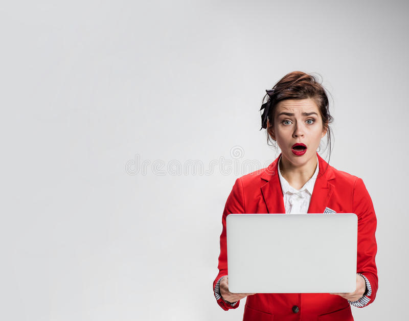 Surprised girl holding laptop over gray background stock image