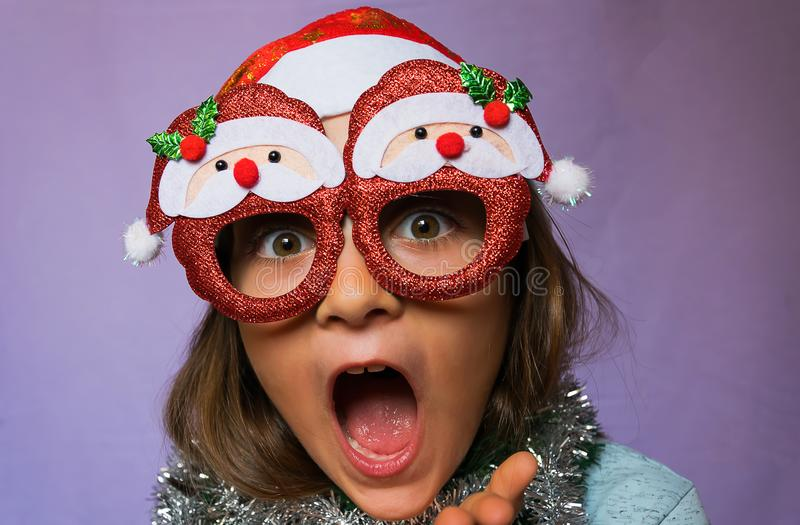 Surprised girl in Santa s hat and glasses. A fun little girl with a hat and glasses Santa Claus surprised for Christmas royalty free stock photos