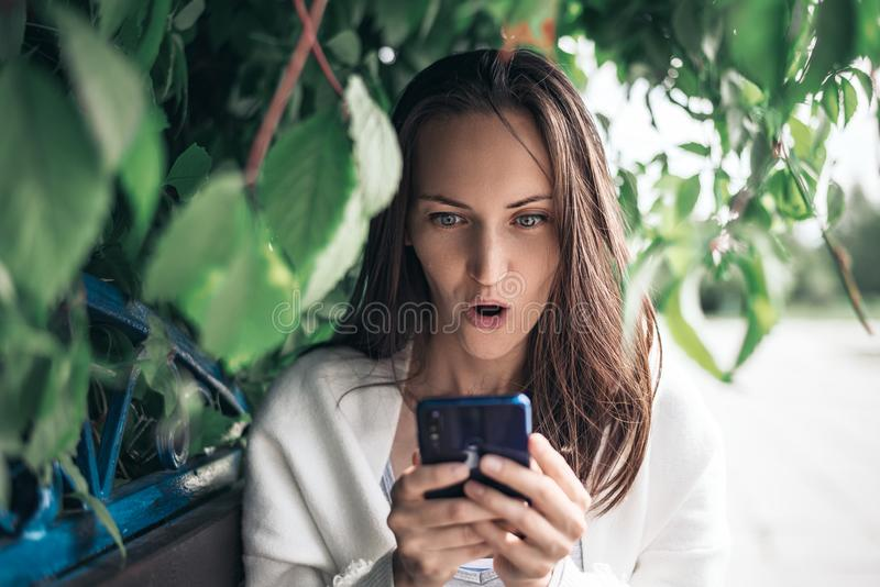 Surprised girl with smartphone in her hands sitting on bench among the leaves royalty free stock image