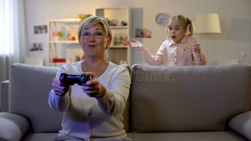 Surprised granddaughter looking at granny playing video game at night, addiction. Stock photo royalty free stock photo