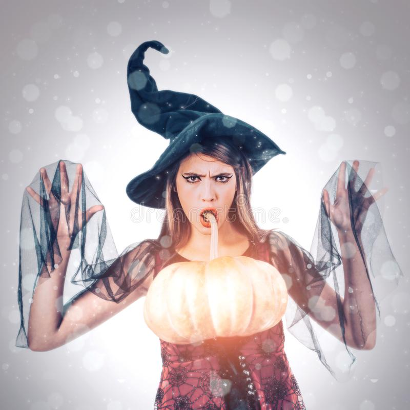Surprised halloween woman. Halloween girl posing with Pumpkin. Beautiful young surprised woman in witches hat and royalty free stock photo
