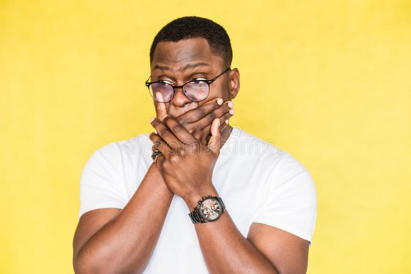 Surprised handsome African American man in glasses covers mouth in shock. stock image