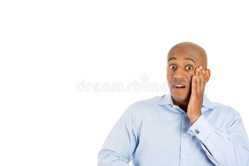 Surprised handsome bald man with hand on cheek