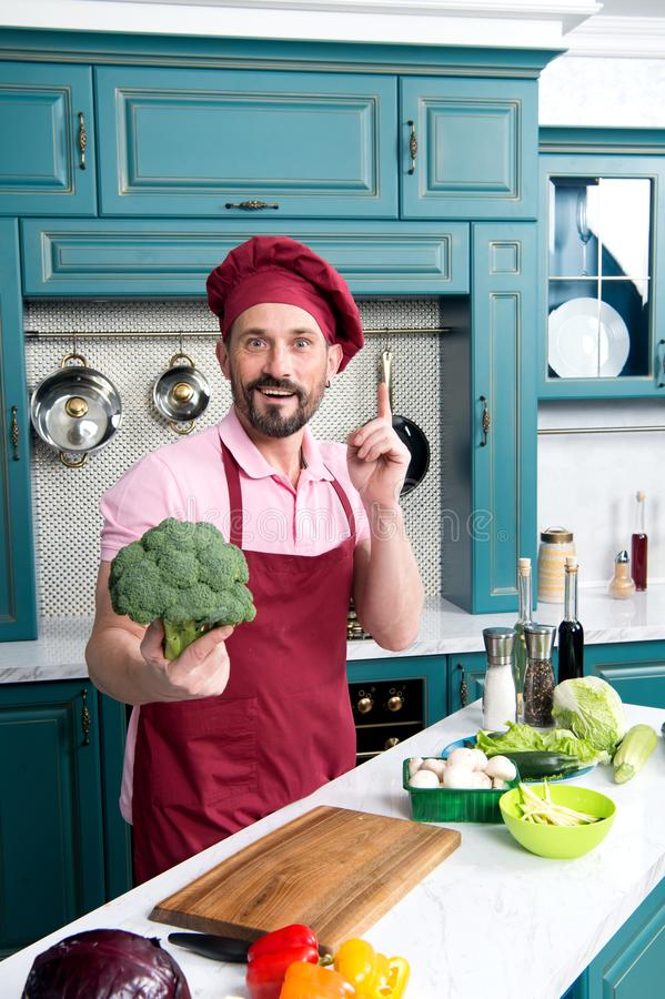 Surprised handsome cook holds broccoli. Fresh broccoli in chef`s hand. Guy pointed broccoli for vegetarian food. Chef in red apro stock photos